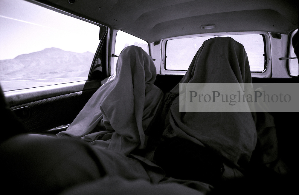 Passengers cover themselve up for a sleep,  while travelling towards Khost on board of a taxicab