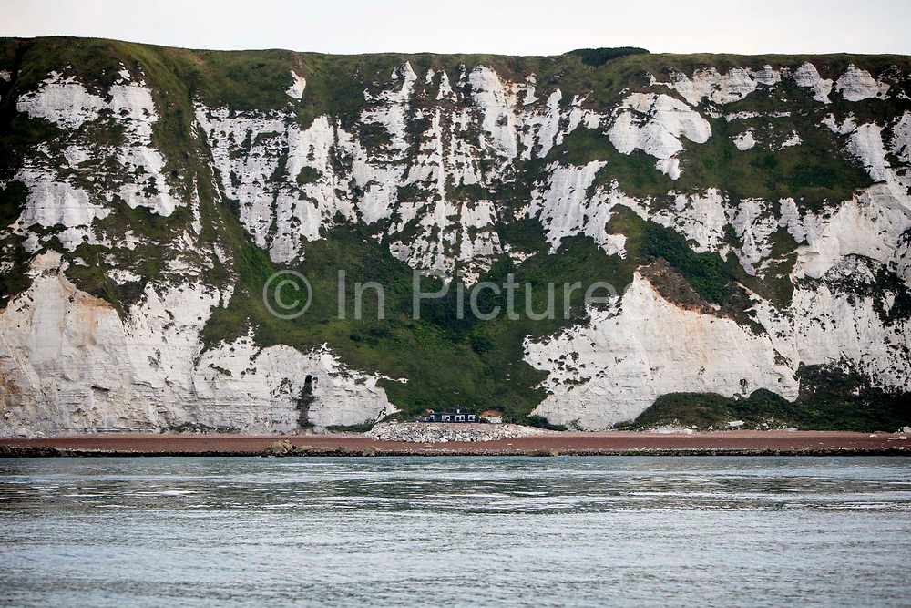 The famous chalky White Cliffs of Dover above The Warren Beach and country park a secluded building sits at the bottom of the cliff on a rock platform on the beach, Folkestone, Kent, England, United Kingdom.