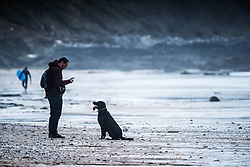A man and his dog at Fistral Beach in Newquay, Cornwall.