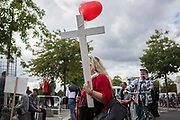 """A participants in """"The March For Life"""" is seen carrying a wooden cross prior to the beginning of the event, in Berlin's Mitte district, on September 16, 2017. In the center of the pro-life event was the call by the organizers for German politicians and society to take active action against a """"silent increase of acceptance"""" of the phenomenon. Abortion in Germany is permitted in the first trimester of the pregnancy, with the condition of mandatory counseling and in a later period of the pregnancy in cases of medical necessity.<br /> (Photo by Omer Messinger)"""