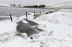 © Licensed to London News Pictures. 13/02/2021. Llanfihangel Nant Melan, Powys, Wales, UK. A bitterly cold landscape by a frozen lake as strong south east winds and snow hit Mid Wales with temperatures minus 4.5 deg C and 'feels like' temperature around minus 10-15 deg C near Llanfihangel Nant Melan in Powys, Wales, UK. Photo credit: Graham M. Lawrence/LNP