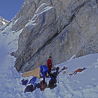 Ski Mountaineers Jay Jensen and Allan Pietrasanta set up an emergency camp after they and the photographer were avalanched down a gully adjacent to this cliff.  This was the first-ever winter traverse of India's Great Himalaya Range from Ladakh to Kashmir. Not knowing that he had suffered two crushed vertebrae and a knee injury Wiltsie was able to ski two more days to the first civilization.