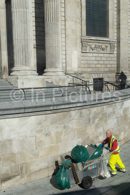 A contract street cleaner pushes a laden bin trolley beneath the tall columns of St Paul's Cathedral, on 5th October 2020, in London, England.