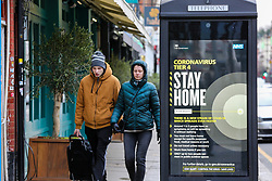 © Licensed to London News Pictures. 26/12/2020. London, UK. A couple in north London walk past the government's 'Coronavirus Tier 4 - Stay Home' publicity campaign poster as many parts of the UK entered the highest level of COVID-19 restrictions on Boxing Day after mutated COVID-19 strains continue to spread around the country. Prime Minister, Boris Johnson refused to rule out a third national lockdown in the New Year. Photo credit: Dinendra Haria/LNP