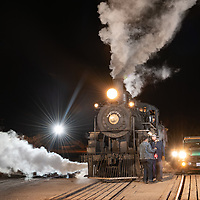 Night image of Hy-rail maintenence car #18 along side Engine #40 in Nevada Northern Rail Yard. Lights in the railkyard and on the maintenance vehicle and locomotive appear as star bursts.