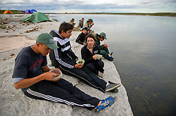 "Den First Nation youth eat dinner on the edge of  the Thelon river in August, 2011.  The Thelon is the largest and most remote game sanctuary in North America, which almost no one has heard of.  For the Akaitcho Dene, the Upper Thelon River is ""the place where God began.""  Sparsely populated, today few make it into the Thelon. Distances are simply too far, modern vehicles too expensive and unreliable. For the Dene youth, faced with the pressures of a western world, the ties that bind the people and their way of life to the land are even more tenuous. Every impending mine, road, and dam construction threatens to sever these connections.(Photo by Ami Vitale)"