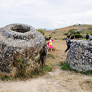 Lao children play among the stone jars at Site 1 of the Plain of Jars in north-central Laos. Much remains unknown about the age and purpose of the thousands of stone jars clustered in the region. Most accounts date them to at least a couple of thousand years ago and theories have been put forward that they were used in burial rituals.
