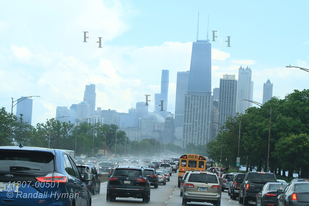 Storm clears over downtown skyline as seen from the north on traffic-packed Lake Shore Drive; Chicago, Illinois.