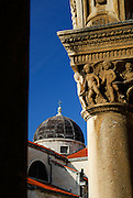 Detail of column carvings, Knezev Dvor (Rector's Palace), with dome of church of Saint Blaise (Sveti Vlaha), Dubrovnik old town, Croatia