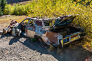 Rusted car detail in the ruins of Idarado Mine, north of Red Mountain Pass along the Million Dollar Highway, in Colorado, USA. Winding through the San Juan Mountains, the Million Dollar Highway is the scenic 25 miles of US Route 550 between Silverton and Ouray. It was named for the twelve miles south of Ouray through the Uncompahgre Gorge to the summit of Red Mountain Pass. As part of the San Juan Skyway Scenic Byway, the Million Dollar Highway twists along sheer cliff edges with hairpin curves and few guardrails, past spectacular yellow foliage colors in autumn.