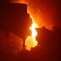 Hot molten metal from blast furnace with orange glow and sparks