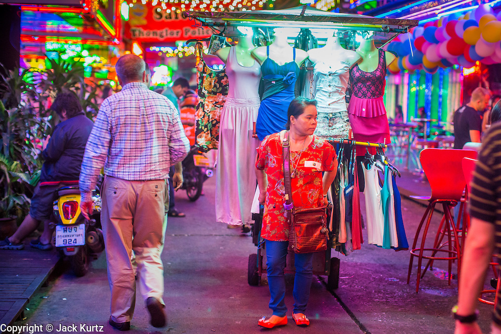 """12 JANUARY 2013 - BANGKOK, THAILAND:  A woman who sells dresses and makeup to the workers in the Soi Cowboy red light district pulls her cart through a throng of tourists on Soi Cowboy in Bangkok. Prostitution in Thailand is illegal, although in practice it is tolerated and partly regulated. Prostitution is practiced openly throughout the country. The number of prostitutes is difficult to determine, estimates vary widely. Since the Vietnam War, Thailand has gained international notoriety among travelers from many countries as a sex tourism destination. One estimate published in 2003 placed the trade at US$ 4.3 billion per year or about three percent of the Thai economy. It has been suggested that at least 10% of tourist dollars may be spent on the sex trade. According to a 2001 report by the World Health Organisation: """"There are between 150,000 and 200,000 sex workers (in Thailand).""""    PHOTO BY JACK KURTZ"""