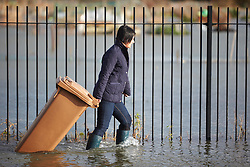 © Licensed to London News Pictures.  09/01/2014. OXFORD, UK. A woman pulls a wheelie bin down a flooded Abingdon Road in south Oxford .  Photo credit: Cliff Hide/LNP