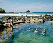 A family paddle and play with a fishing net whilst three elderly women swim in Portreath Pool, Cornwall, UK. Created by adding a retaining wall to a rock pool, until the 1970s this tidal pool was used by a local school for swimming lessons. Until the 1950s and the rise of the heated indoor swimming pool, children learnt to swim outdoors. For those close to the sea, many man-made tidal swimming pools were constructed around Britain's coastline. Heated by the sun, these tidal pools were often built to keep bathers safe from high and rough seas, which explains why so many of them are clustered in Scotland and around the surfing beaches of Cornwall. Whether they are simple swimming holes made by shoring up natural rock pools or grand lido-like pools complete with lifeguards and tea huts, they are all refreshed by good high tides.