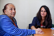 Paralegal Romina Kajtazova is holding hands with NGO Kham client Sazije Fazlievik at the office of the organisation in the city of Delcevo, Macedonia.