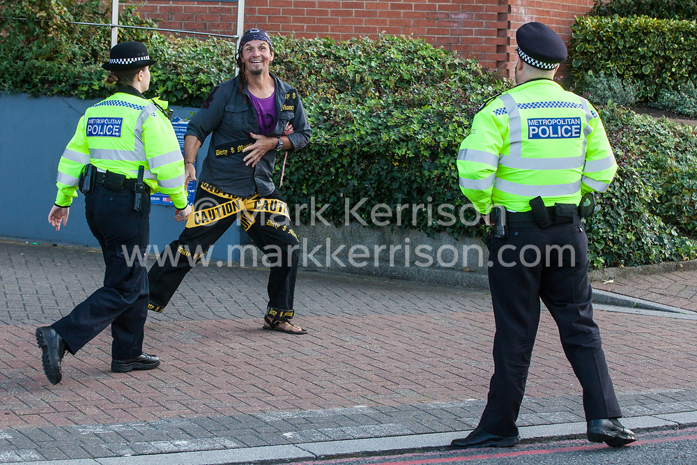 London, UK. 7 September, 2019. A Metropolitan Police officer chases an activist who she feared might attempt to block the road on the sixth day of Stop The Arms Fair protests outside ExCel London against DSEI, the world's largest arms fair. The sixth day of protests was billed as a Festival of Resistance and included performances, entertainment for children and workshops as well as activities intended to disrupt deliveries to ExCel London for the arms fair.