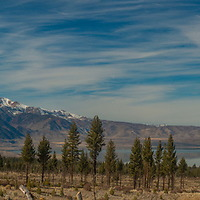 Cirrus clouds drift over Mono Lake and the eastern Sierra Nevada Crest.  The Mono Craters rise to the left.