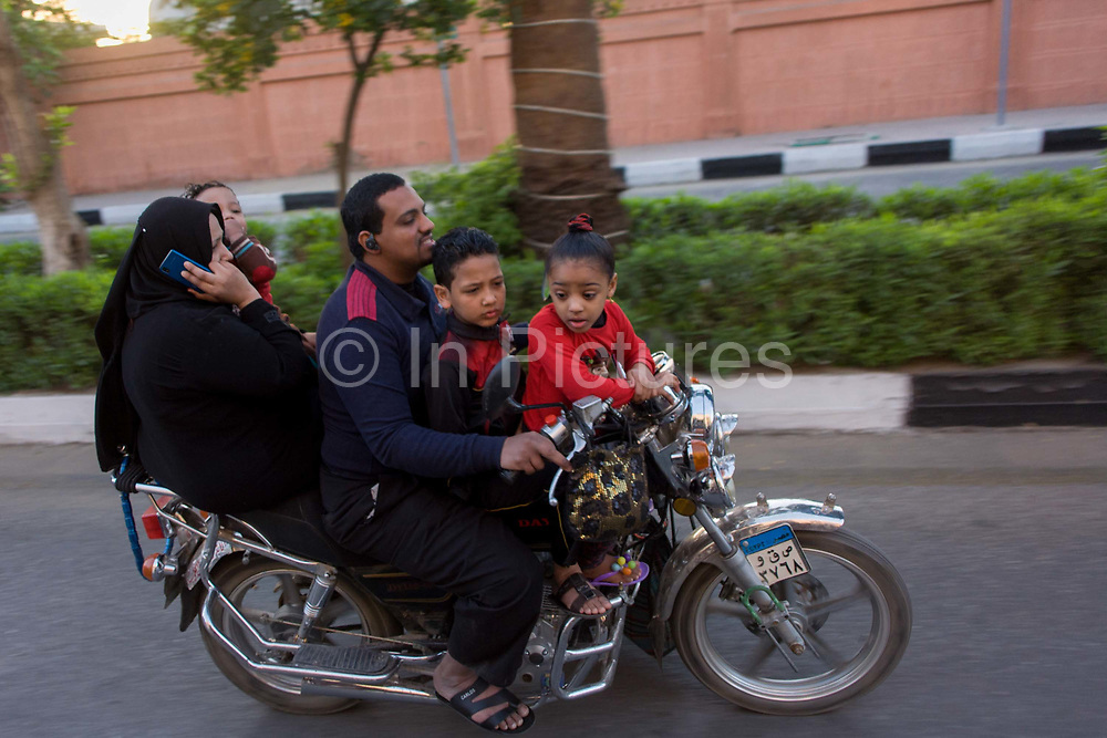 A family of rive ride fast on a motorbike on a road in modern Luxor, Nile Valley, Egypt. Speeding alongside a calesh carriage, the family overtake, the father driving the bike with two small children at the front with mother talking on the phone and a smaller child held too. Health and safety is barely understood in an Egyptian city.