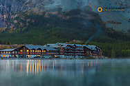 Many Glacier Lodge reflects into Swiftcurrent Lake at dawn in Glacier National Park, Montana, USA