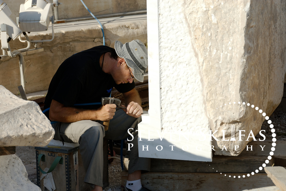 Acropolis. Athens. Greece. View of a work man, a modern marble sculptor delicately chiselling a large block of Pentelic marble as part of the Parthenon and Acropolis restoration project. The Acropolis of Athens and its monuments are a UNESCO World Heritage Site.