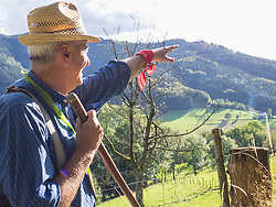 Senior man pointing towards mountain in Middle Black Forest, Baden-Wuerttemberg, Germany
