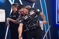 Gerwyn Price swats a fly during the William Hill World Darts Championship Semi-Finals at Alexandra Palace, London, United Kingdom on 2 January 2021.