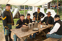 Bob Beausoleil, Corporal Larry Gilman, Kelly Hoyt, Evelyn Duffy, Bob Duffy, Captian Rick Goodwin and Private Howard Leonard assemble around the table of their Civil War encampment at the NH Veterans Association compound off Lakeside Avenue in the Weirs  Sunday morning.  (Karen Bobotas/for the Laconia Daily Sun)