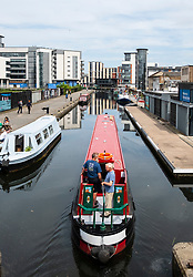 View of Union Canal at Lochrin Basin with narrow boat sailing to mooring at Fountainbridge in Edinburgh, Scotland, United Kingdom, UK