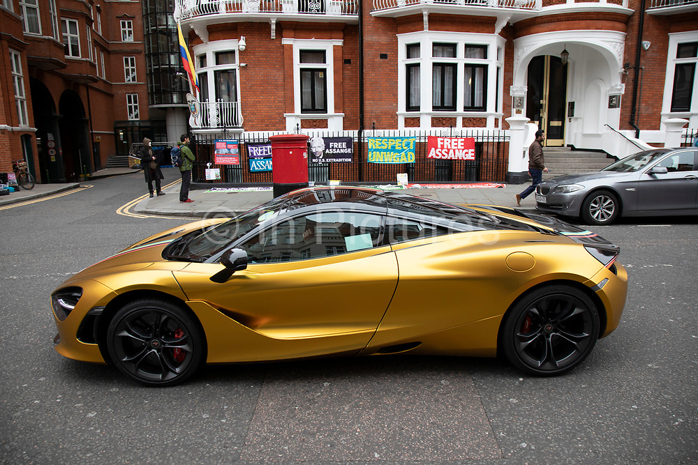 Gold McLaren sports car in the wealthy area of Knightbridge in London, United Kingdom. This is an area where the rich in their supercars parade them around driving with little more reason than showing off their exclisive cars.