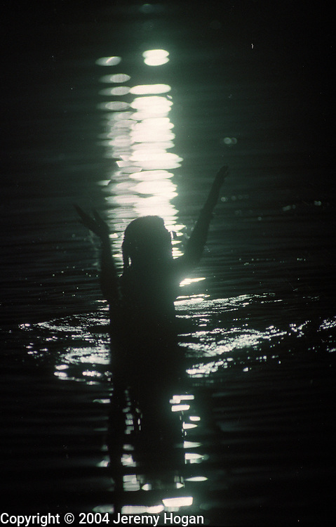 Copyright ©Ê2004 Jeremy Hogan - All Rights Reserved..A female deadhead skinny dips in a pond after a riot during the Grateful Dead show at Deercreek, Indiana during July 1995. ..Generation x, genx, grateful dead, deadhead, deadheads, dropout, hippy, hipster, hip, traveler, youth culture, journey, Americana, 90s, 1990s, counterculture, woman, skinny dip, night, sillouette, arms raised,