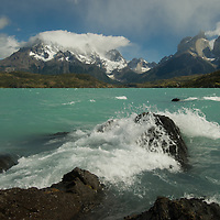 Wind-driven waves on Lake Pehoe crash ashore  under the Grand Tower of Paine and the Horns of Paine in Torres del Paine National Park, Chile.