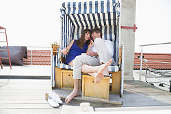 Couple eating strawberry in roofed wicker beach chair, smiling