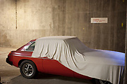 Covered MGB GT car in an underground garage makes for a ghostly figure.