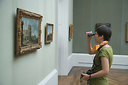 young woman using binoculars to study an old style painting Metropolitan Museum of Art New York