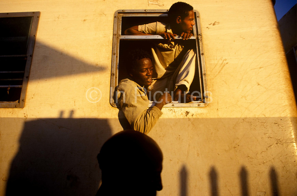 Men hanging out of the window on the train between Djibouti and Addis Ababa. The rail line originally built by the French in 1897 over 20 years, is the only route from Addis Ababa and the sea at Djibouti.