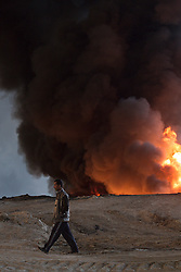 Licensed to London News Pictures. 20/10/2016. An Iraqi man walks past a burning oil well, one of several located on the edge of the neighbourhood where he lives in Qayyarah, Iraq. The wells, part of a large oilfield around the town, were set alight by retreating Islamic State militants in July 2016, but have yet to be extinguished. <br /> <br /> Since being retaken from the Islamic State the town of Qayyarah has become an important staging post for the Iraqi Army, and some US support elements, in the buildup to the Mosul offensive. Photo credit: Matt Cetti-Roberts/LNP