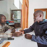 CAPTION: The programme has helped Jean Claude gain the trust of his local microfinance institution, SACCO. Concern would distribute payouts through SACCO, and he intends to approach them soon to get a loan to pay off the remainder of what he owes for the motorbike he bought. His motorbike taxi service brings him a profit of roughly FRW 100,000 to FRW 120,000 per month, and after paying for the month's repayment instalment there is little left for living on. He is therefore seeking FRW 400,000 from SACCO to help him through the final four months of repayments. Once he is through the hire-purchase term, the motorbike will start generating significant profits for him. LOCATION: Rugarama Village, Kiruhura Cell, Rusatira Sector, Huye District, South Province, Rwanda. INDIVIDUAL(S) PHOTOGRAPHED: Deogratias Mazimpaka (left) and Jean Claude Minani (right).