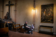 Bologna, 11 may 2018, Grandfather waiting with his grandchild inside the Santo Stefano, the oldest church in town.