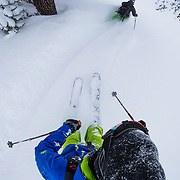 Tyler Hatcher skis Cascade powder during winter from a POV camera angle behind photographer Jay Goodrich.