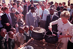 """Embargoed to 0001 Monday August 21 File photo dated 12/07/93 of children wait in line as Diana, Princes of Wales lends a hand to serve the food at the Child Feeding Scheme at Nemazuva Primary School in Zimbabwe. Diana, Princess of Wales was a woman whose warmth, compassion and empathy for those she met earned her the description the """"people's princess""""."""