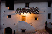 Whitewashed render of a rural farmhouse in Steinegger, Eppan-Appiano in South Tyrol, Italy. It is early evening and the light from an overhead light in the porch. The province's unemployment rate is 3.3%.