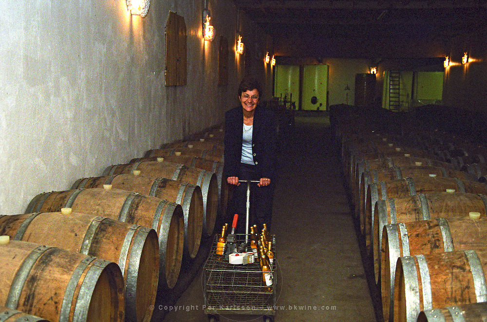 """Madame Marie-Josée Pierre owner of Chateau Caillou in the barrel aging cellar pushing a """"shopping cart"""" trolley with wine bottles at Chateau Caillou in Sauternes. Josee  Chateau Caillou, Grand Cru Classe, Barsac, Sauternes, Bordeaux, Aquitaine, Gironde, France, Europe"""