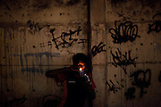 "In this Aug. 7, 2012 photo, a man smokes crack in the Manguinhos slum in Rio de Janeiro, Brazil. <br /> <br /> <br />  The South American country began experiencing a public health emergency in recent years as demand for crack boomed and open-air ""cracolandias,"" or crack lands, popped up in the sprawling urban centers of Rio and Sao Paulo, with hundreds of users gathering to smoke the drug. The federal government announced in early 2012 that more than $2 billion would be spent to fight the epidemic, with the money spent to train local health care workers, purchase thousands of hospital and shelter beds for emergency treatment, and create transitional centers for recovering users."