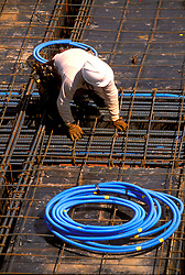 Stock photo of a construction worker prepares a steel rebar framework before a concrete pour.
