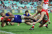 Nathan Djerrkura of the Bulldogs is tackled over the boundary line by Daniel Hannebery of the Swans during the AFL Round 18 match between the Sydney Swans and the Western Bulldogs at the SCG, Sydney.