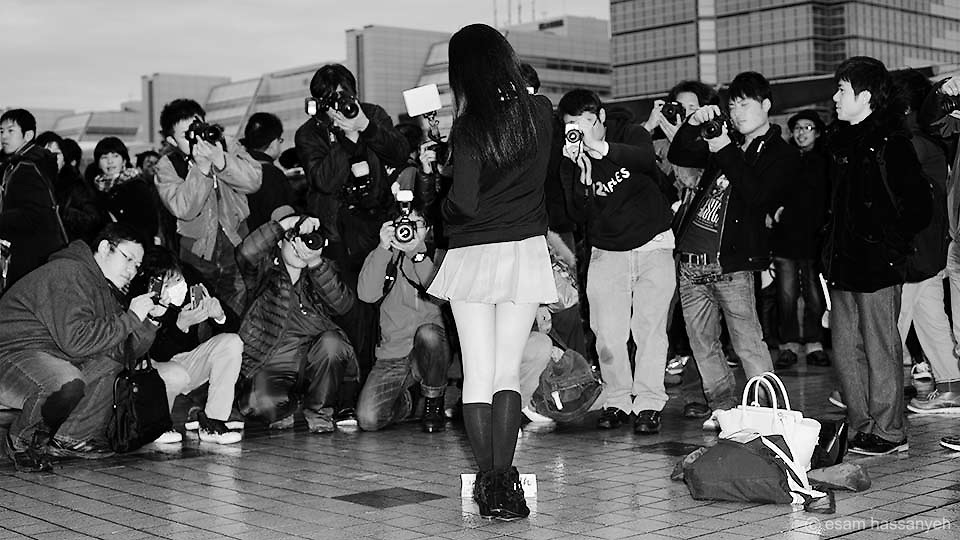 Photographers huddle to take a photo of a young Japanese girl as Comiket Tokyo.