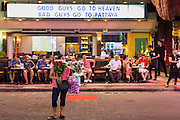 """26 SEPTEMBER 2014 - PATTAYA, CHONBURI, THAILAND: A woman sells flowers in front of a go-go bar on Walking Street in Pataya. Pataya, a beach resort about two hours from Bangkok, has wrestled with a reputation of having a high crime rate and being a haven for sex tourism. After the coup in May, the military government cracked down on other Thai beach resorts, notably Phuket and Hua Hin, putting military officers in charge of law enforcement and cleaning up unlicensed businesses that encroached on beaches. Pattaya city officials have launched their own crackdown and clean up in order to prevent a military crackdown. City officials have vowed to remake Pattaya as a """"family friendly"""" destination. City police and tourist police now patrol """"Walking Street,"""" Pattaya's notorious red light district, and officials are cracking down on unlicensed businesses on the beach.     PHOTO BY JACK KURTZ"""