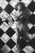 Black and white photo of nude woman laying on checkered tile floor with arms across her chest and satin draped over her hips