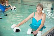 Senior living women doing water aerobics with weights