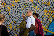 Tourists finding their way around London's Soho and the West End seek help with a large city map. A middle-aged tourist couple have stopped during their exhausting tour of London on foot, pausing to consult the large-scale plan of the capital's streets where landmarks, shops and the river Thames in context are shown as places of interest. Standing near the image of the map, there is also a circle denoting the radius of a 5-minute walk from this location in Leicester Square. The round line appears to encircle their upper bodies in a humorous scene of tourism and discovery, of adventures in the metropolis and of the facilities that Westminster council provide for their visitors.